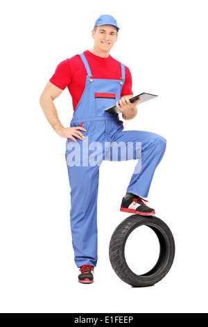 Full length portrait of a mechanic holding a clipboard - Stock Photo