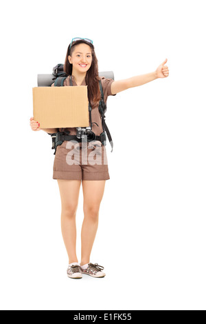 Full length portrait of a female hitchhiker holding a blank carton sign - Stock Photo