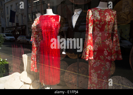 Red dresses for sale in the Dolce and Gabbana shop on Bond Street, London, UK. - Stock Photo