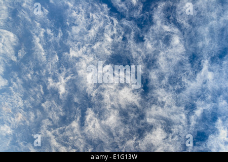 cirrocumulus lacunosus fluffy clouds in blue sky - Stock Photo