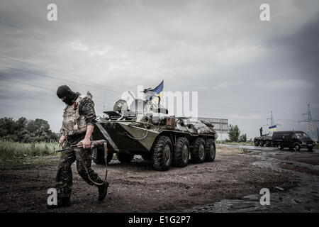 Donetsk, Ukraine. 31st May, 2014. Soldier passes the APC on the check-point next to Slaviansk city, on May 31, 2014. - Stock Photo