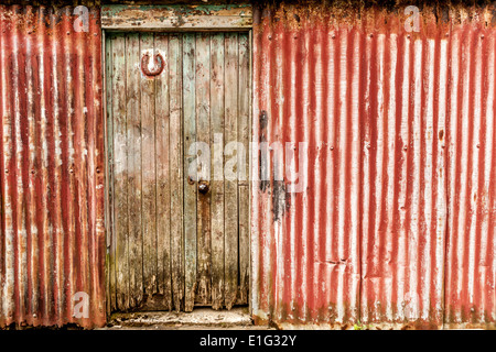 A corrugated sheet building with a door and a lucky horse shoe hanging on the door. - Stock Photo