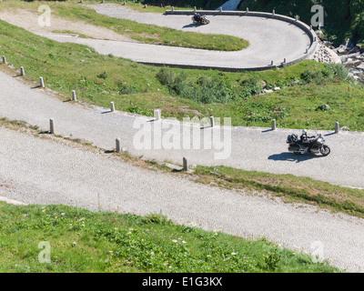 Motorbike tourists drive up the cobble stone paved road ('Tremola') on the historic mountain pass of San Gottardo, - Stock Photo