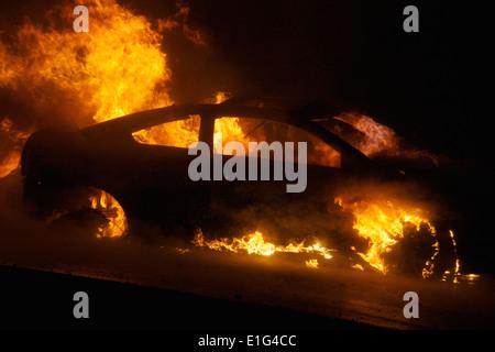 Car burns down through the dead of night. - Stock Photo