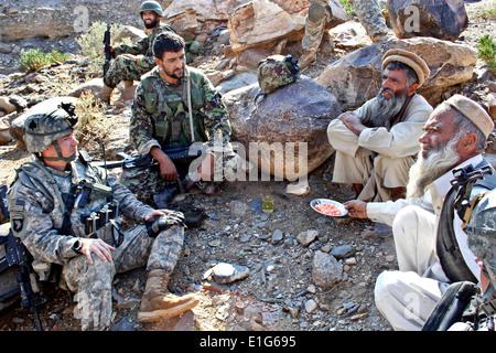 U.S. Army 2nd Lt. Daniel Wild, left, and an Afghan army weapons team leader talk with Gurem village elders Nov. - Stock Photo