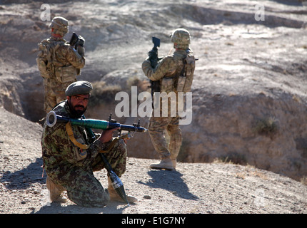 An Afghan National Army soldier, center, provides security with U.S Soldiers from 4th Brigade Combat Team, 10th - Stock Photo