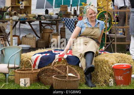 Land girl ww11 sitting on straw bales and union Jack Flag at a Nostalgia show - Stock Photo
