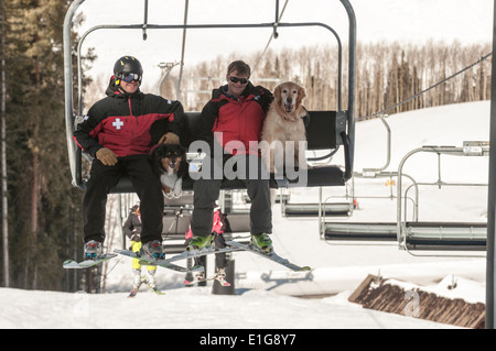 Two male ski patrollers riding lift with their search dogs while working at the Crested Butte Ski Resort, Crested - Stock Photo