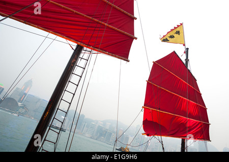 Traditional Red-Sailed Chinese junk in Victoria Harbour, Hong Kong - Stock Photo