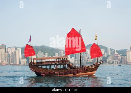 A tourist tour junk crosses Victoria Harbour, Hong Kong - Stock Photo