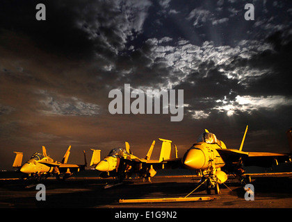From left, a U.S. Marine Corps F/A-18C Hornet and two Navy F/A-18E-F Super Hornet aircraft are illuminated by lights - Stock Photo
