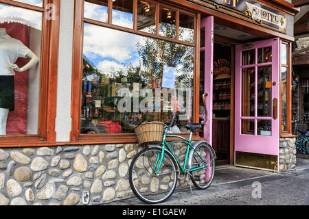 Cruiser bicycle with basket outside a storefront, Banff, Alberta, Canada - Stock Photo