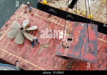 National Steel and Shipbuilding Company shipyard workers use a barge crane to move the propellers and rudder of - Stock Photo