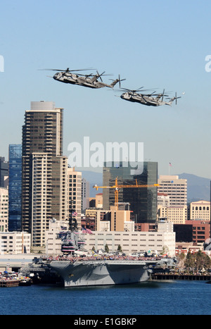 A formation of U.S. Navy CH-53 Super Stallion helicopters fly past the USS Midway Aircraft Carrier museum during - Stock Photo