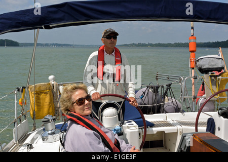 Couple in the cockpit of Viking Mariners Bénéteau Océanis Clipper 473 cruising yacht Viking Blue on the River Orwell, - Stock Photo
