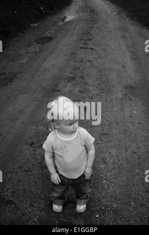 Young toddler girl standing on a dirt track road looking to one side. - Stock Photo