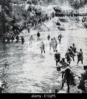 British colonial African soldiers cross a river in East Africa during World War One - Stock Photo