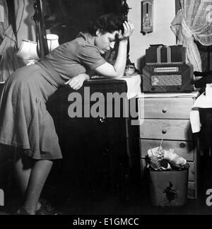 Photograph of a woman listening to a murder mystery on the radio in a boarding house. Dated 1943 - Stock Photo