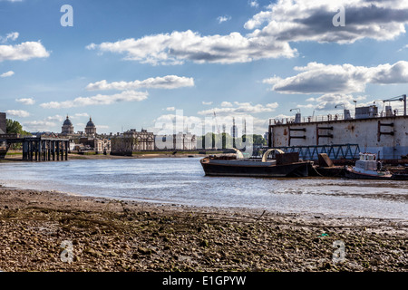 View from Thames river Path at low tide - exposed riverbed, boats, Old Royal Naval College and Greenwich Power station - Stock Photo