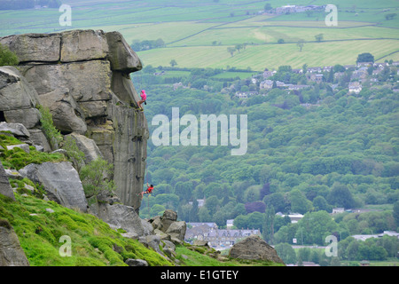 Abseiling down the Cow and Calf rock face on Ilkley Moor West Yorkshire England UK - Stock Photo