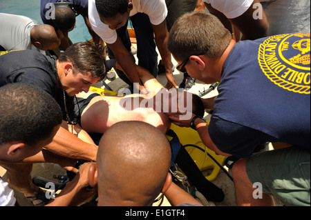 Members of Mobile Diving and Salvage Unit (MDSU) 2 and multinational divers load U.S. Navy Chief Hospital Corpsman - Stock Photo
