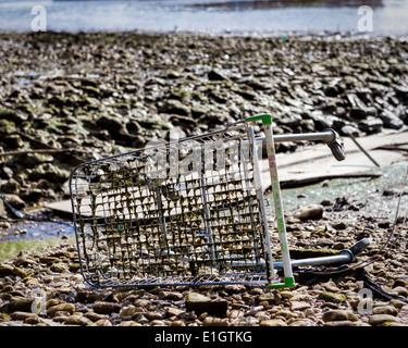Old rusty discarded Asda shopping trolley in the exposed riverbed of the River Thames at low tide, Greenwich, London, - Stock Photo
