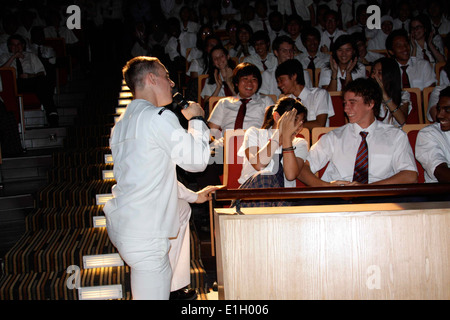U.S. Navy Musician 3rd Class Gabriel Brown, with the 7th Fleet Band's Orient Express, sings to a student during - Stock Photo