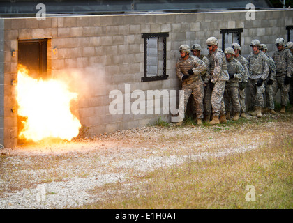 U.S. Soldiers stand back from a fire during military operation in urban terrain and breaching sapper training at - Stock Photo