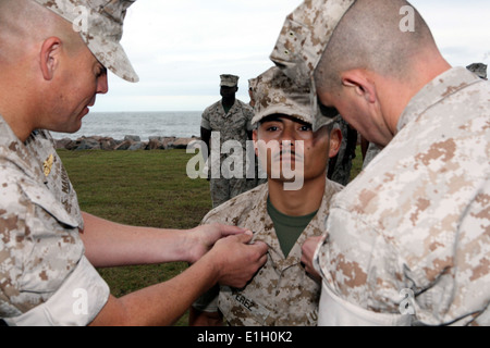 U.S. Marine Corps Staff Sgt. Tomas Perez has new chevrons pinned to his uniform by Capt. Scott Benninghoff, a logistics - Stock Photo