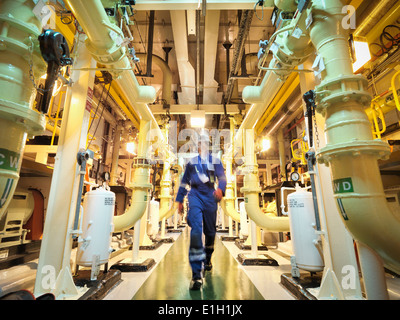 Engineer walking amongst pipes of nuclear power station - Stock Photo