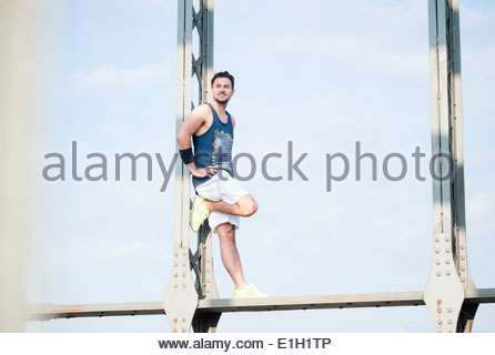Jogger leaning against steel structure - Stock Photo