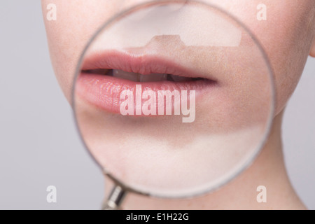 Portrait of young woman, magnifying glass on mouth - Stock Photo