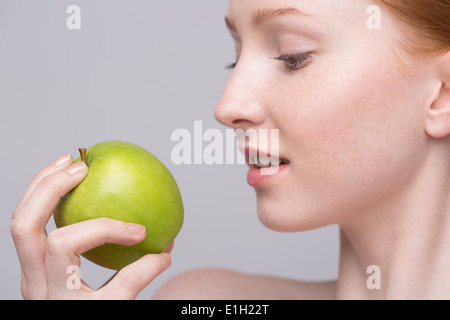 Portrait of young woman, holding green apple - Stock Photo