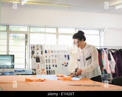 Fashion designer cutting cloth in fashion design studio - Stock Photo