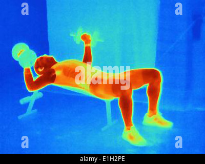 Thermal image of an athlete training with weights. The image shows the heat produced by the muscles - Stock Photo