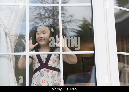 Young girl looking out from sitting room window - Stock Photo