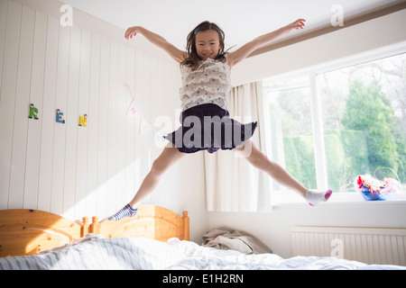 Young girl jumping mid air on bed - Stock Photo