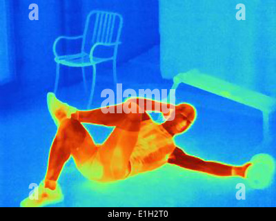 Thermal image of young male athlete in training. The images shows the heat produced by the muscles - Stock Photo