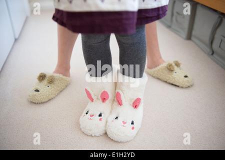 Children wearing animal slippers