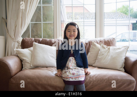 Portrait of young girl sitting on sofa - Stock Photo