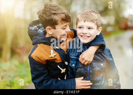 Brothers hugging outdoors - Stock Photo