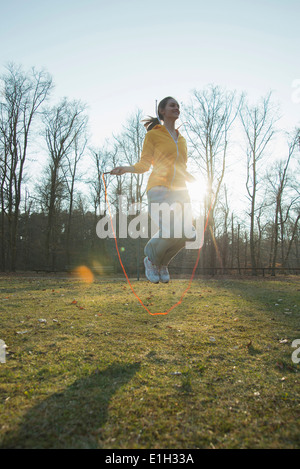 Young woman exercising in field with skipping ropes - Stock Photo