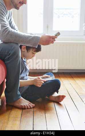 Father and son spending time in living room - Stock Photo