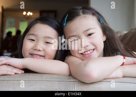 Portrait of two young girls leaning on sofa - Stock Photo