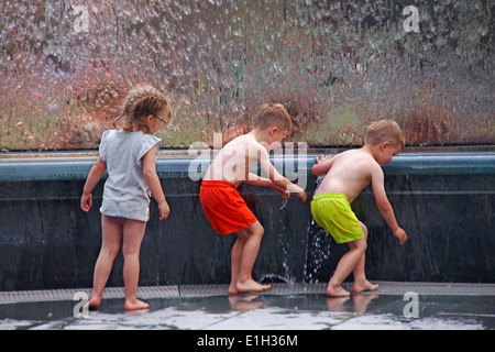 enjoying the water - children playing in water fountains at Millenium Square, Harbourside, Bristol in May - Stock Photo