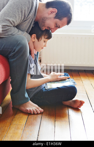 Father and son using digital tablet - Stock Photo