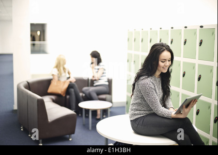 Young woman sitting on table using digital tablet - Stock Photo