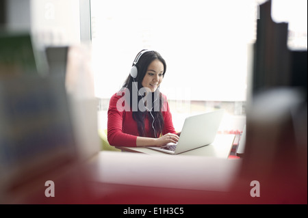 Young woman wearing headphones using laptop - Stock Photo