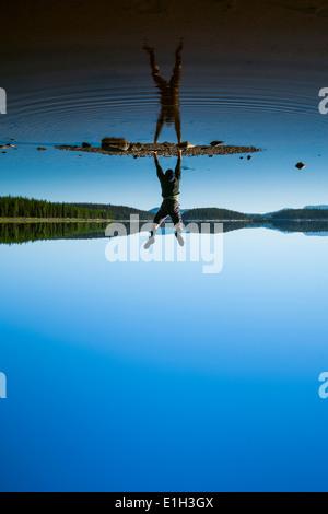 Man doing handstand at McCulloch Lake along the KVR trail, Okanagan Highlands, British Columbia, Canada - Stock Photo