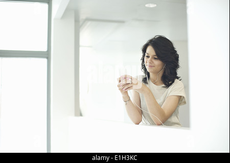 Young women using mp3 player - Stock Photo